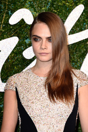 Cara Delevingne wore her tresses down in edgy side-swept layers during the British Fashion Awards.