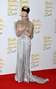 Daphne has a flare for the dramatic. Here she dons a floor length silver gown with tulle covering her shoulders.