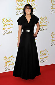 Samantha weras a floor length black gown with a structured A-line silhouette.