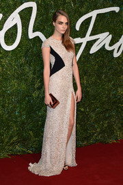 Cara Delevingne complemented her glam dress with a geometric black, red, and gold clutch.