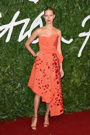 Karolina Kurkova brought a bright pop to the British Fashion Awards red carpet with this asymmetrical orange strapless dress featuring red appliques and a bowed waist.