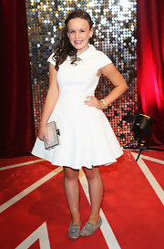 Ellie Leach complemented her simple dress with a pair of sparkly silver smoking slippers.