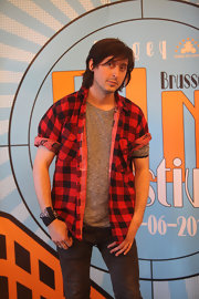 Carl Barat added some fun to his outfit by mixing patterns with a striped knit top under his flannel shirt.