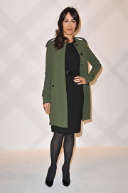 Dolores Chaplin gave a peek of her little black dress under her army green coat for the Burberry Paris Boutique opening.