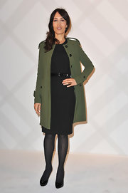 Dolores Chaplin looked undeniably chic in a collarless sage wool coat and a classic black sheath dress.