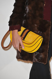 Anja Rubik brightened up her ensemble with a yellow leather clutch at the opening of Burberry's Paris boutique.