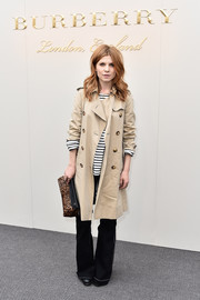 Clemence Poesy teamed a beige Burberry trenchcoat with a black-and-white striped sweater for the label's fashion show.