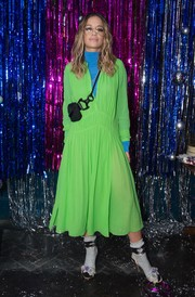 Rita Ora layered a loose neon-green midi dress over a blue turtleneck for the Burberry x Cara Delevingne Christmas party.