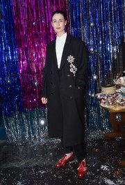 Erin O'Connor was masculine-chic in an oversized, bejeweled black coat at the Burberry x Cara Delevingne Christmas party.