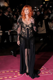 Cher wore a seductive lace and chiffon gown with fishnet stockings and fiery orange wig.