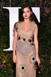 Selena Gomez attended the #BoF500 gala carrying an elegant black and gold tube clutch by Tod's.