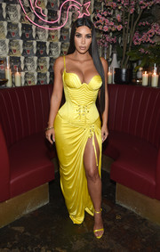 Kim Kardashian was in figure-flaunting mode, as always, in this high-slit yellow corset gown by Versace at the Business of Fashion dinner.