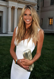 With her dress, Elle carrys a gold metallic clutch. This color becomes glamorous when paired with white.