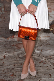 Harley Viera-Newton carried a stand-out orange quilted clutch bag by Chanel for a Chanel dinner.