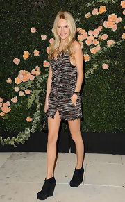 Poppy Delevigne was chic in tweed at the Chanel soiree. She topped off her look with black suede wedge booties.
