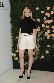Elle Fanning showed some leg at the Chanel dinner in a pair of loose white high-waisted shorts.