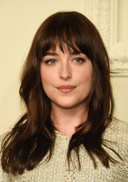 Dakota Johnson opted for a casual, subtly wavy 'do with wispy bangs when she attended the Chanel Paris-Salzburg show.