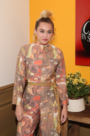 Miley Cyrus styled her graphic jumpsuit with a gold rope belt for the world premiere of 'Crisis in Six Scenes.'