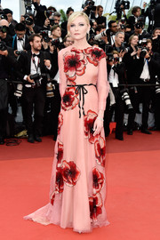 Kirsten Dunst oozed ultra-feminine appeal in a floral-sequined coral gown by Gucci at the Cannes opening gala.