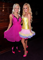 Holly posed with her co-star in a vibrant pink v-necked dress with a matching pair of pink satin pumps. The cute bow detail on the back added some fun flare to the super girlie design.