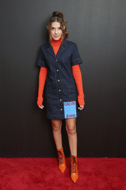 Millie Bobby Brown layered a denim dress over a bright red turtleneck for the Calvin Klein Spring 2019 show.