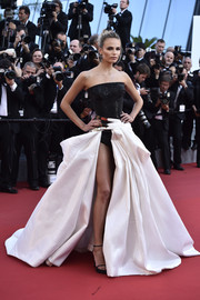 Natasha Poly looked bold and sexy at the 'Carol' premiere in an Atelier Versace gown featuring a sparkly black bodysuit and a white ball skirt with a leg-revealing gap.