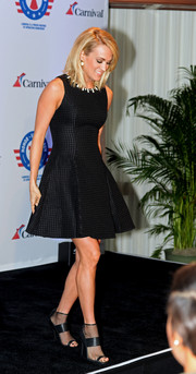 Carrie Underwood kept it youthful and elegant in a textured black skater dress during the announcement of her partnership with Carnival Cruise Line.