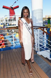 Deshauna Barber layered a gold satin duster over a little white dress for her visit to the Carnival Vista cruise ship.