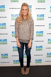 Carrie Underwood visited the Z100 Elvis Duran morning radio show wearing a pair of tan suede cutout booties.