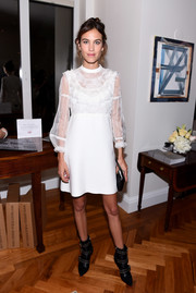 Alexa Chung looked angelic in a white ruffle cocktail dress by Miu Miu at the 'Vogue - Voice of a Century' celebration.