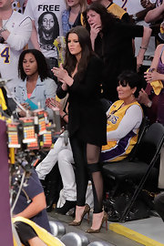 Khloe looked stylish while sitting courtside in glittery Louboutin pumps and sheet paneled leggings.