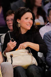 Julia Louis-Dreyfus looked stylish at the Lakers game with this nude chain-strap bag and draped blouse combo.