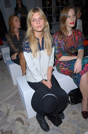 Clemence Poesy donned a silky button down blouse with sheer navy lace during London Fashion Week.