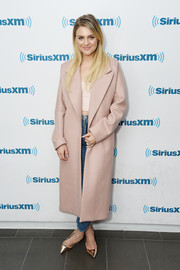 Kelsea Ballerini layered a blush-colored wool coat over a crop-top and jeans for her visit to SiriusXM.