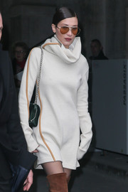 Bella Hadid stayed warm and stylish in a leather-trimmed turtleneck dress by Celine while attending Paris Fashion Week.