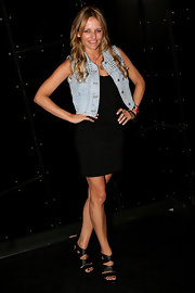 Zoe shows off her strappy black heels while posing for cameras at the Chadwick model agency cocktail party. Her jean vest adds a hint of edge to her little black dress, which tie in well with her multi-strap heels.