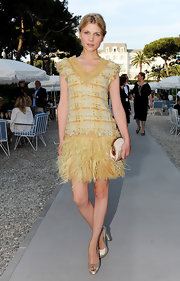 Clemence Poesy teamed her flirty yellow feathered and tweed Chanel dress with champagne satin peep-toes.