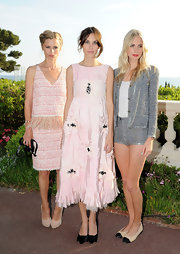 Poppy Delevigne teamed her darling tweed shorts with classic nude and black captoe flats.