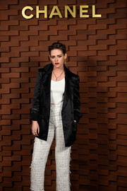 Kristen Stewart was androgynous-chic in a black satin blazer layered over a white crop-top at the Chanel Collection Metiers d'Art Paris Hamburg show.
