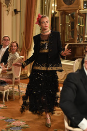 Cara Delevingne showed off a gorgeous dress featuring gold sequin detailing and a ruffle skirt at the Chanel Collection des Métiers d'Art show.