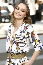 Lily-Rose Depp teamed a gold belt with a graphic shirtdress, both by Chanel, for the brand's Cruise 2020 show.