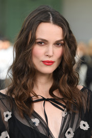 Keira Knightley's red lipstick look striking against her alabaster skin.