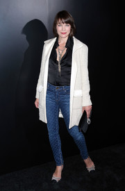 Milla Jovovich was casual yet sophisticated in a black satin button-down shirt while attending the Chanel dinner.