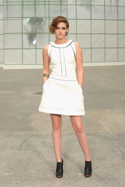 Kristen Stewart teamed her dress with black lace-up booties by Chanel.