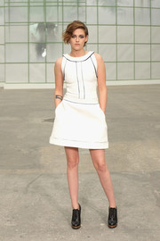 Kristen Stewart kept it breezy and cute at the Chanel Couture show in a white mini dress with black piping.