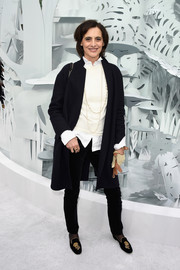 Ines de la Fressange completed her menswear-inspired ensemble with a pair of flower-embellished smoking slippers.