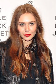 Elizabeth Olsen added some pop to her glowing skin by sporting this red lip color.