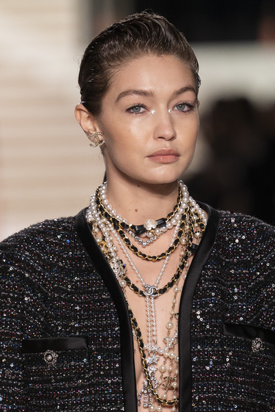 Gigi Hadid accessorized with a ton of pearl and leather necklaces.