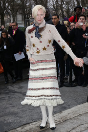 Tilda Swinton attended the Chanel fashion show wearing a fun-looking star-embellished nude sweater from the brand.