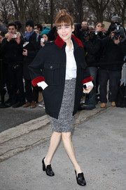 Marie-Jose Croze attended the Chanel fashion show wearing a blue military jacket with a red collar and cuffs.